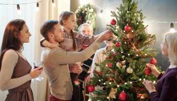 family cheerily decorating christmas tree thanks to these holiday safety tips