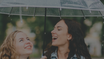 Two women smiling underneath umbrella