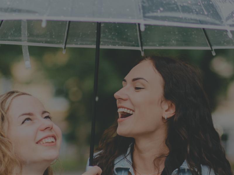 Two women smiling underneath umbrella metaphor for what is umbrella insurance