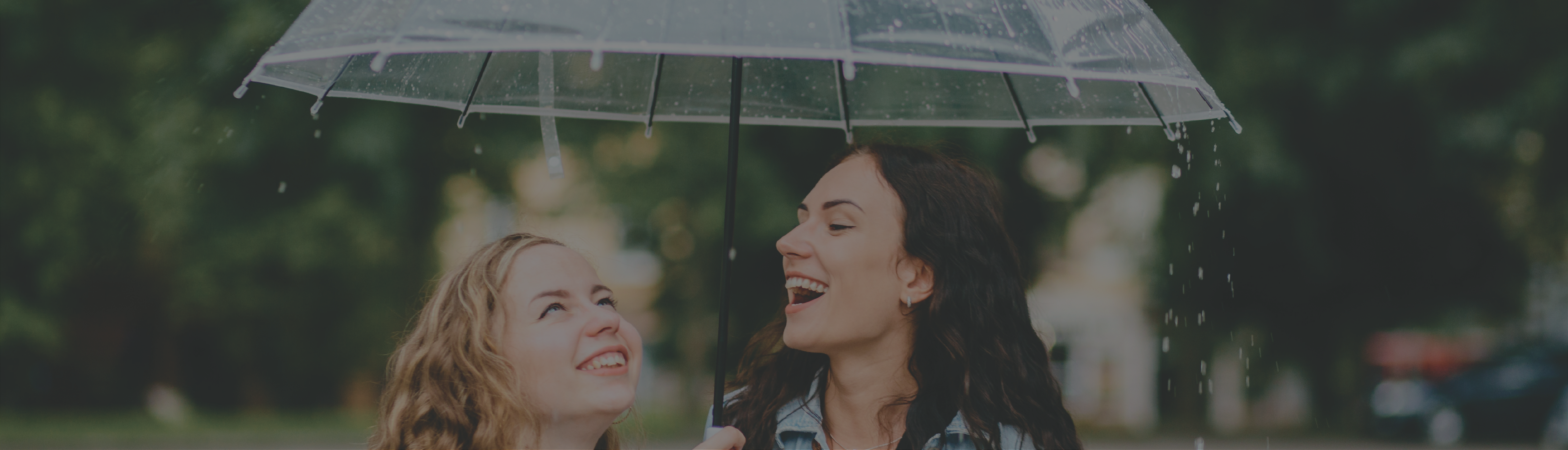 Two women smiling underneath umbrella metaphor for what is umbrella insurance