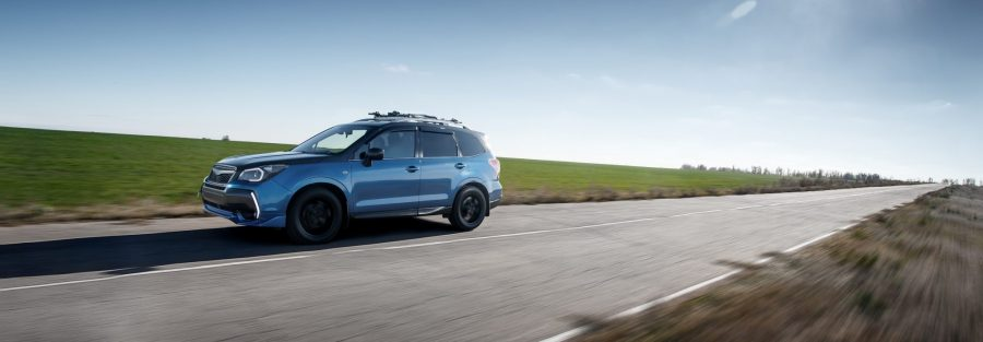 Blue SUV driving down country road