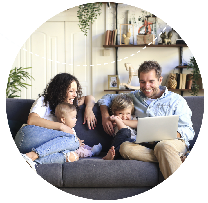 Family relaxing on couch and looking at laptop computer